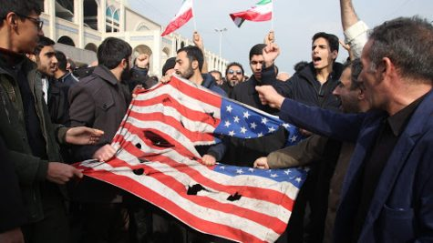 "Iranians tear up a US flag during a demonstration in Tehran on January 3, 2020 following the killing of Iranian Revolutionary Guards Major General Qasem Soleimani in a US strike on his convoy at Baghdad international airport. - Iran warned of ""severe revenge"" and said arch-enemy the United States bore responsiblity for the consequences after killing one of its top commanders, Qasem Soleimani, in a strike  outside Baghdad airport. (Photo by ATTA KENARE / AFP) (Photo by ATTA KENARE/AFP via Getty Images)"