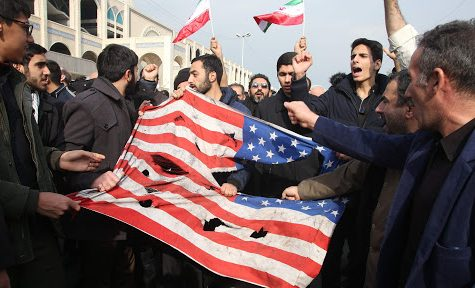 Iranians tear up a US flag during a demonstration in Tehran on January 3, 2020 following the killing of Iranian Revolutionary Guards Major General Qasem Soleimani in a US strike on his convoy at Baghdad international airport. - Iran warned of